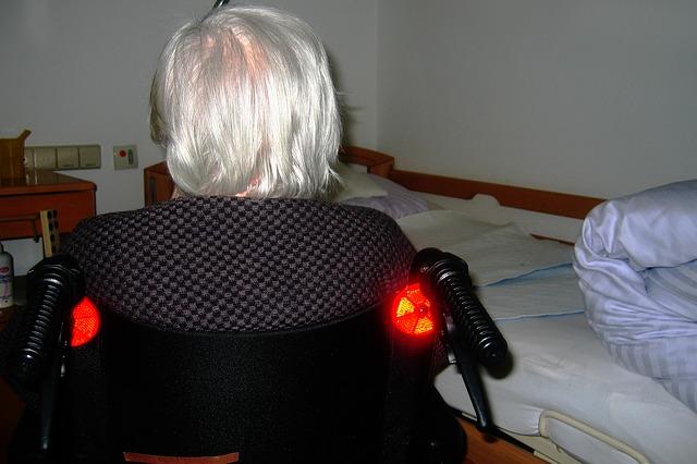 alte Frau im Rollstuhl vor Pflegebett